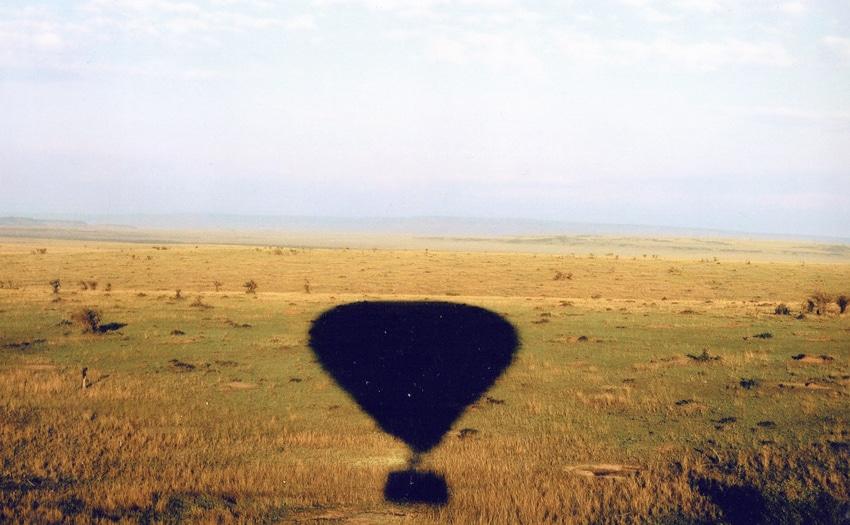 Hot-air balloon's shadow over African plain
