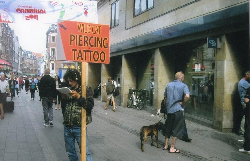Man holding tattoo shop sign in Copenhagen, Denmark
