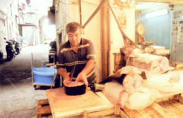 Man preparing swordfish for selling in market