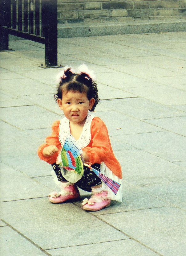 Girl-squatting in bright clothing in Shaanxi Province China
