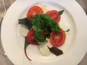Insalata Caprese: Tomatoes, buffalo mozzarella, sweet basil, salt and olive oil. The colours of the Italian flag.